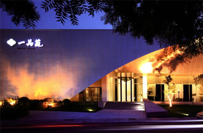 文章导读:对于一品苑接待中心的规划,售楼处设计公司所希望创造的不只是所谓的豪宅质感,而是以创作艺术品般的态度进行设计,不断的雕琢增加其价值。下面就和上海勃朗设计小编一起来感受现代风范的高端售楼部设计案例!  建筑体以造型十足简单的立方体利落的切割、挖空,配上流畅的钢骨玻璃帷幕与具退缩效果的绿意景观,为售楼部营造出一个视线无限延伸的主体立面与走道。   售楼部的接待大厅以挑高光墙作为视觉精神的焦点与诠释,柜台区则以高亮度镜面与墨玻形成简约的对比。会客区刻意以大面留白的轻隔间定义,平行视线高度处,横向挖空处理