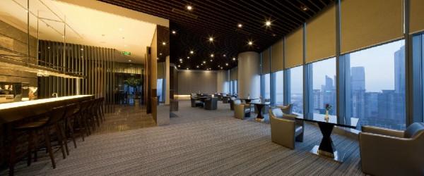 文章导读:本会所位处青岛繁华的半岛CBD内超高层商业大楼里的24层,专供大楼里的酒店住户健身及用餐使用。整体会所设计围绕着两个主轴:刚柔并济与云顶绝境。   穿过狭长的梯厅空间后,一转身是十米面宽尺度放大的大厅,地面是水纹咖啡和意大利灰两种石材。接待台背景墙是一幅贝壳马赛克的拼贴,打上灯光后显得波光粼粼,其间还点缀了绿色系马赛克,在整体刚强大气的空间感中增添纤细柔美。   男女各自穿过更衣室后台阶向上进入泳池层,24米长的水道满足了运动需求的使用者,朝南向的按摩池则让想放松的客人在此远眺海湾,池底为大图案