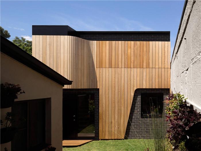 文章导读:厄斯金内威尔工作室,原本就是一处住宅,将来将用作艺术工作室和家庭办公室。该项目的特点是高水平的充满美学的外部设计。下面,上海勃朗办公室设计公司的小编与您分享的就是这间办公室设计案例。  建筑材料主要为黑色釉砖,辅以雪松木坂包墙系统。木板包墙系统兼具了功能性和装饰性,在北面它以旋转百叶窗的形式出现,以其旋转的角度形成色彩和色调的渐变变化。   木质材料与砖材相结合,使整个外观更加的素朴雅致。木板表皮将作为一条丝带,环绕着并遮蔽着建筑自身,并提供流动的、特定方向的视线。   来源:http://ww