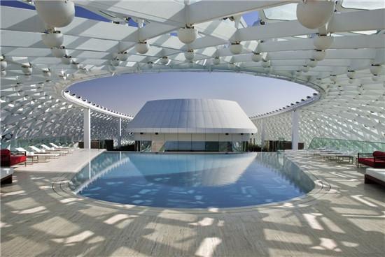 文章导读:本案是一个宾馆项目,名叫烨思酒店,位于阿布扎比,建成于2009年,酒店外观极为美丽,室内空间也很是精致。今天,上海勃朗专业酒店设计公司小编与您分享的就是这个华美的建筑!   酒店外观极为壮观,网状的结构覆盖体,由曲线状钢材打造而成,还有钻石状的玻璃板作为装饰,为宾馆建筑增添了一丝艺术风味。外观自身产生的光影效果也极为精彩,红、蓝、紫等与自然色彩交辉相应,格外美观。   本案酒店设计不仅美在外观,更成于室内。酒店室内空间宽敞明亮,整洁大方。酒店客房空间舒适雅致。简单却又精致的家具、温暖的灯光打造,