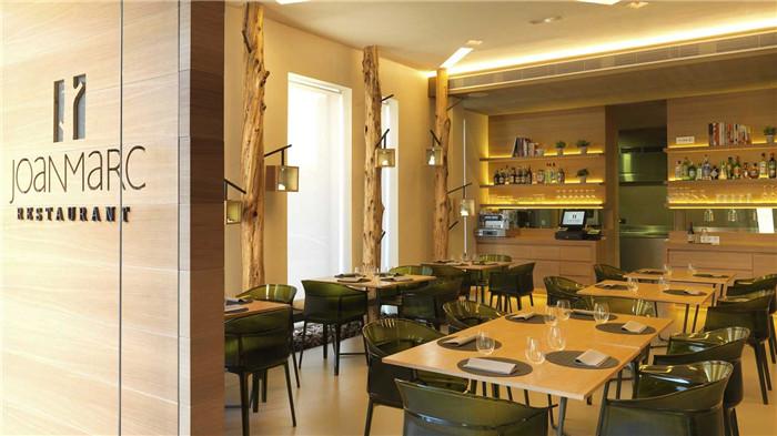 文章导读:Joan March环保主题餐厅位于马略卡岛的中心印加市,坐落在一个角落里,毗邻一个安静而迷人的广场,广场上种植了丰富的当地植物和松树。提供的地中海佳肴是选用最优质而新鲜的本地产品精心制作而成的。   在通往主厅区的橡木入口上,雕刻着餐厅名字Joan March的艺术字体。主厅区新安装着高而窄的窗户,让食客能欣赏到外面的风景。同时,人一般长短的树杆用来装饰室内,让人产生无限的幻想。    餐厅设计分为三个区域,首先是一个沙发座位区,有一组古灯照亮这里;主餐厅区,Kartell的橄榄绿Papiro