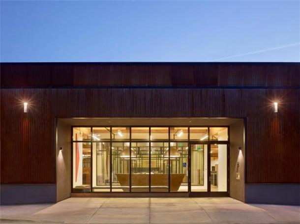 文章导读:这是位于美国加州的办公建筑,建筑改造主要围绕四个方面:工业化的审美外观;巧妙的将一天中不同的时光反映在室内的自然光变化上;使用精心挑选的材料以及最大化的利用建筑空间。   建筑的外墙上开着暗黑色金属框架的窗子,深深的窗口用黑色的金属板遮挡办公室原先的出口正对着公路,办公室设计师把它改成正对着停车场,这样是为了增强公司的隐秘性,为员工们提供更高的私密空间。   玻璃墙隔开的户外院落和休息室,则营造出了分层的透明空间,给人一种宽敞开放的感觉。那些黑色的金属框架,却给这里平添了几分阳刚的气息。   来