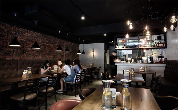 文章导读:「老仓库」店如其名,利用大量仓库元素如红砖、水泥粉光、铁件吊灯等,构筑店内主视觉,搭配复古的老式家电单品,就着晕黄的灯光与墙上老照片,彷彿将时空拉回1930年代。   整体餐厅设计色调沉稳,由墨黑、深灰与暗红、赤褐等色组成,散发静谧气息。店内用餐区域分别设为走道两侧,左侧长型钉扣沙发延伸至店面底部,让视觉延展最大化,并与后方红砖墙完美搭配,营造浓厚美式仿旧风格。    右侧灰质墙面让光影更有发挥的空间,在纯黑的天花与轨道照明包覆下,悬吊的裸式灯泡更显得别具复古风情。利用复古元素与室内外的明暗对比