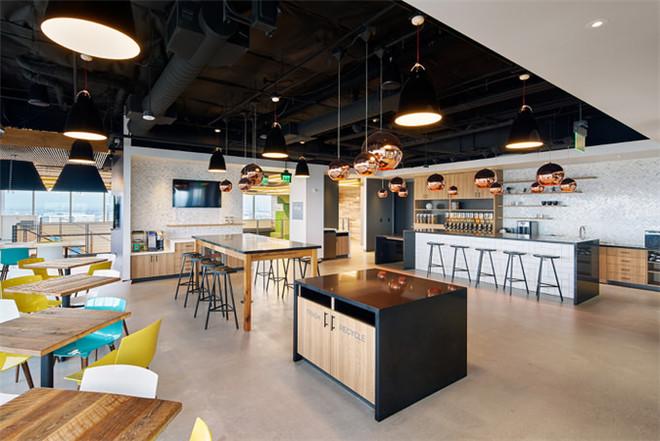 文章导读:这是位于美国的Malwarebytes网络安全公司的办公室,新的办公空间更加宽敞,能够更好的满足公司办公需求。下面,就同郑州办公室装修设计公司勃朗空间设计小编一起欣赏这个办公室吧。   编织的地毯、墙画,以及定制的彩色灯具,共同构建出的是一个层次感强烈而且精致复杂的办公空间,设计师考虑到了房间内的每一处细节设置。明亮的蓝色和黄色,还有中性化的黑色背景,再配上有机的木头家具,以及从那些大窗户里透进来的自然光,这一切在室内混合出一种不可思议的美。   钢材、黄铜、石头、大理石、以及咖啡区和员工共用