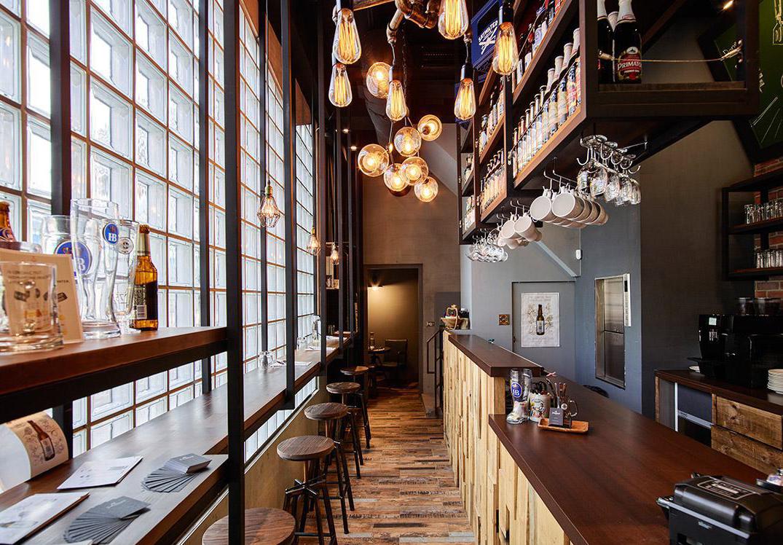 文章导读:座落在学区附近的德式料理餐厅,业主偏爱复古、怀旧的质感,且特别提出天花板希望以黑色呈现。综观以上条件,专业餐厅设计公司建议能将整体风格定调为工业风,强调利用家具与软件的搭配,堆栈精彩的个性表情,并融入大量木质元素,营造出朴质自然的德式乡村情境。   一道砌砖矮墙与三角花圃,将室外座位区和店面明确与大马路做出区隔,醒目的铁制招牌经过特殊锈化处理,展现斑驳仿旧的视觉效果,独特的风格特色让人第一眼就留下深刻印象。木质元素从户外座位区开始蔓延入室内,考量餐饮空间的清洁便利性,地坪特别选用木纹款式的复古地